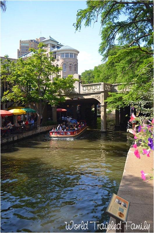 Boats travel down the San Antonio Riverwalk